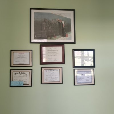 a framed picture and framed diplomas/certifications on a wall
